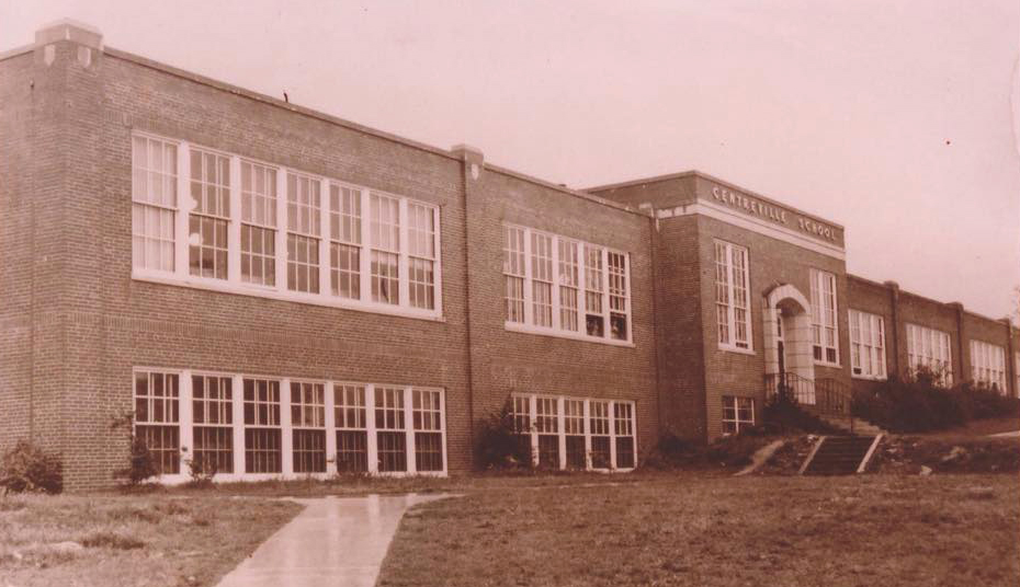 Sepia-toned photograph showing an angled view of the old brick Centreville Elementary School. The building is two stories tall and has a sidewalk and concrete stairway leading to an arched entryway. The rows of windows are painted white and two children are visible, peering out from two open windows in the distance.