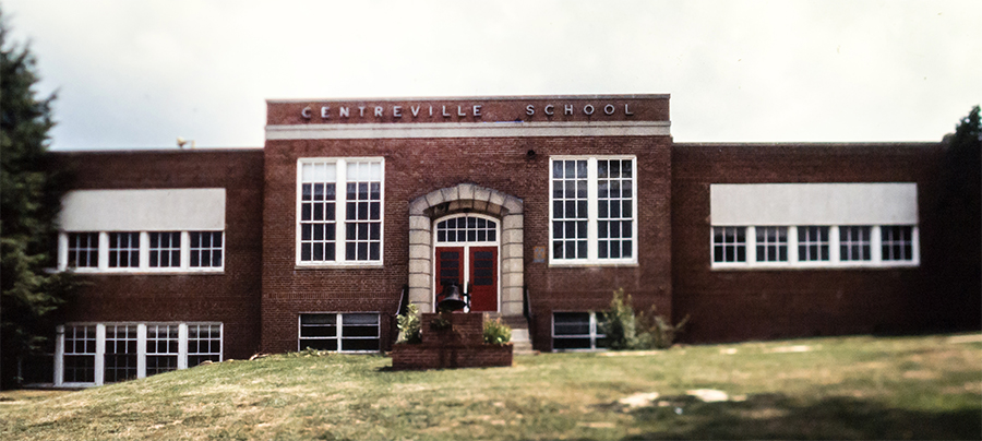 Undated color photograph of the first brick Centreville Elementary School building. The bell that used to be on the three-room schoolhouse is mounted on a brick platform in front of the main entrance.