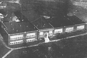 Black and white aerial photograph of Centreville Elementary School taken in the 1950s after additional classrooms have been added to the building.