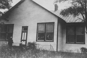 Black and white photograph of the three-room Centreville Elementary School taken by the Virginia Department of Education in 1933. This photograph is of the opposite side of the building that was shown earlier on this page. Two men wearing hats are standing next to what appear to be the rear door of the building.