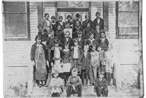Black and white Centreville Elementary class photo from 1924. 28 students and their teacher are lined up on the steps to the main entrance of the three-room schoolhouse.