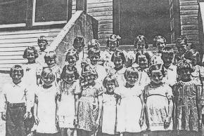 Black and white Centreville Elementary class photo from the 1938 to 1939 school year. The young children are lined up in three rows on the steps of the school entrance. 23 children are pictured.