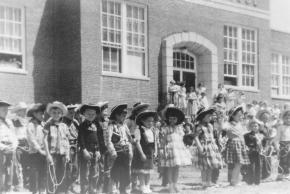 Black and white photograph of Centreville School's May Day celebration in 1957. The children, in western-themed attire, are lined up in front of the school wearing cowboy hats. The boys are wearing vests and plaid shirts, and some hold rope lassoes. The girls are also wearing hats, and have plaid skirts and dresses.